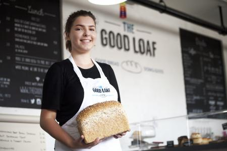 The Good Loaf woman serving a freshly baked loaf